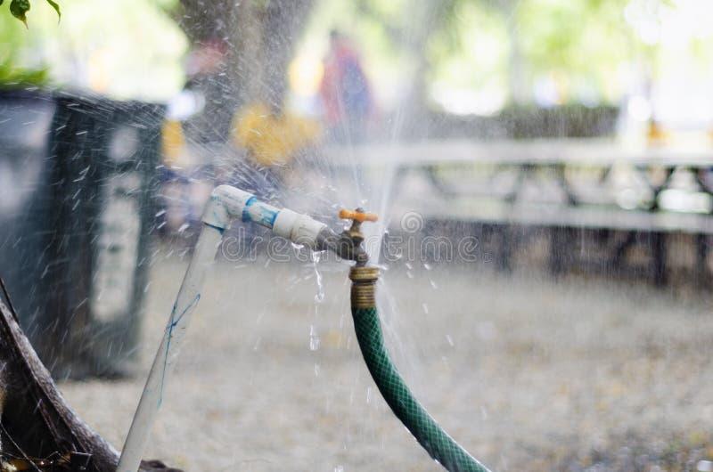 Η στρόφιγγα κήπων που σπαταλά το νερό με την ψύξη της στρόφιγγας κήπων που σπαταλά το νερό με την ψύξη του ναυπηγείου σύνδεσε με  στοκ εικόνες
