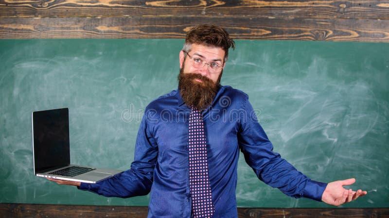 Η συγκεχυμένη δάσκαλος έκφραση Hipster κρατά το lap-top Ζητήματα εξ αποστάσεως εκπαίδευσης Γενειοφόρος συγκεχυμένη άτομο εργασία  στοκ φωτογραφίες