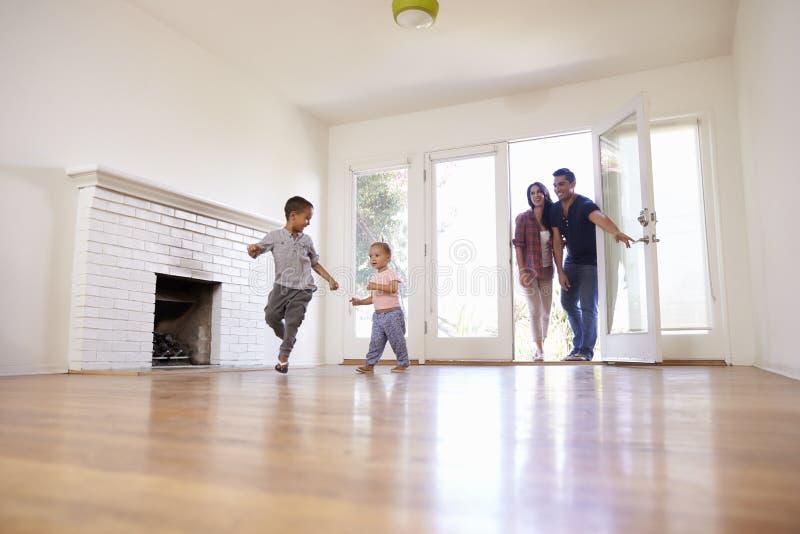 Η συγκινημένη οικογένεια ερευνά το νέο σπίτι στην κίνηση της ημέρας στοκ εικόνα
