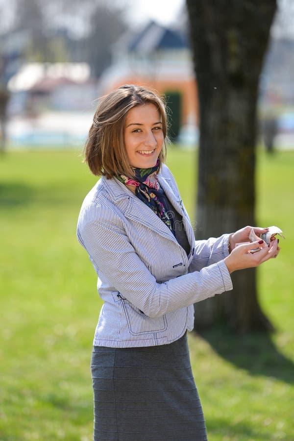 Η συγκινημένη χαριτωμένη γυναίκα μετρά τα χρήματα στο πάρκο στοκ εικόνες με δικαίωμα ελεύθερης χρήσης