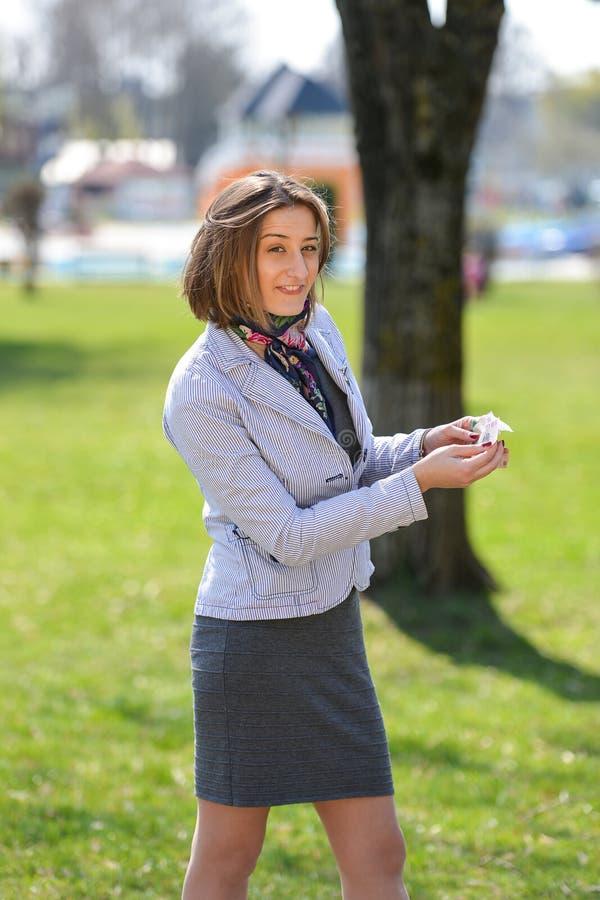 Η συγκινημένη χαριτωμένη γυναίκα μετρά τα χρήματα στο πάρκο στοκ εικόνα