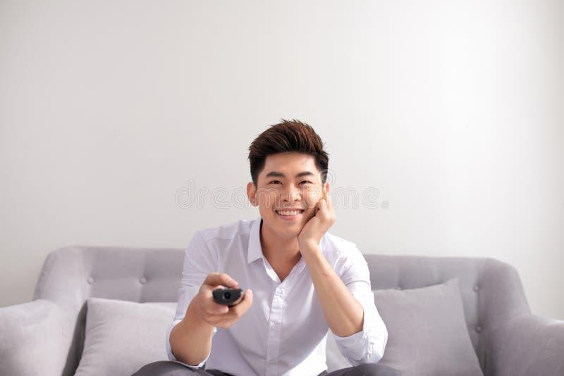 Η συγκλονίζοντας TV παρουσιάζει Όμορφος νεαρός άνδρας που κρατά τον τηλεχειρισμό και στοκ φωτογραφία με δικαίωμα ελεύθερης χρήσης
