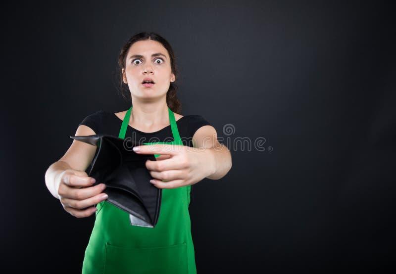 Η συγκλονισμένη νέα γυναίκα παρουσιάζει κενό πορτοφόλι της στοκ εικόνες