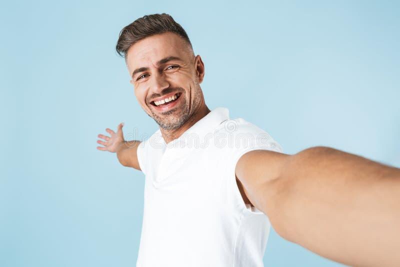 Η συναισθηματική ενήλικη τοποθέτηση ατόμων που απομονώνεται πέρα από το μπλε υπόβαθρο τοίχων παίρνει ένα selfie από τη κάμερα στοκ φωτογραφία με δικαίωμα ελεύθερης χρήσης