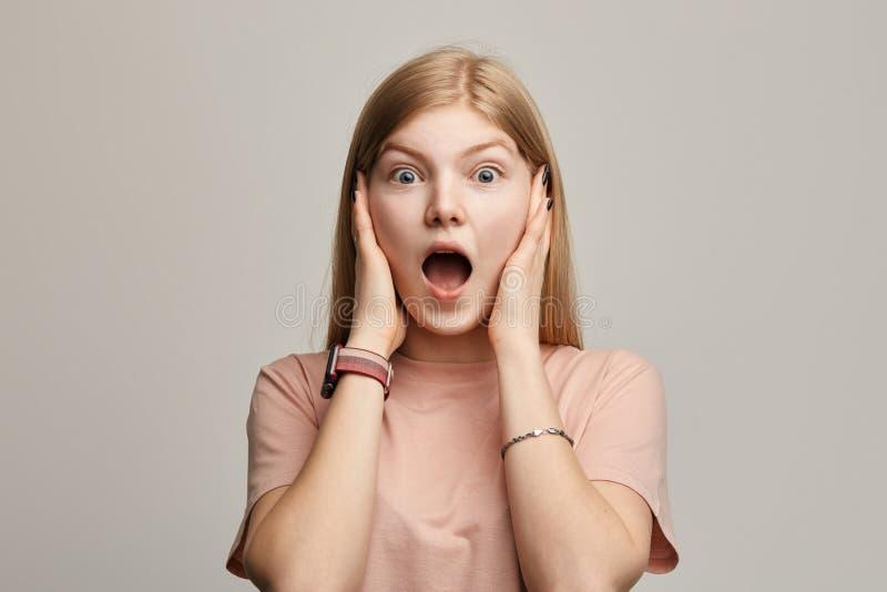 Η συναισθηματική φοβησμένη γυναίκα με τη μακριά δίκαιη τρίχα κρατά τους περίβολους τα αυτιά της στοκ εικόνα