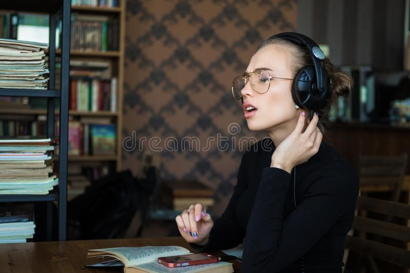 Η συνεδρίαση γυναικών σπουδαστών στη βιβλιοθήκη και το τραγούδι ακούοντας τη δυνατή μουσική μέσω των ακουστικών σύνδεσαν με στοκ φωτογραφία με δικαίωμα ελεύθερης χρήσης