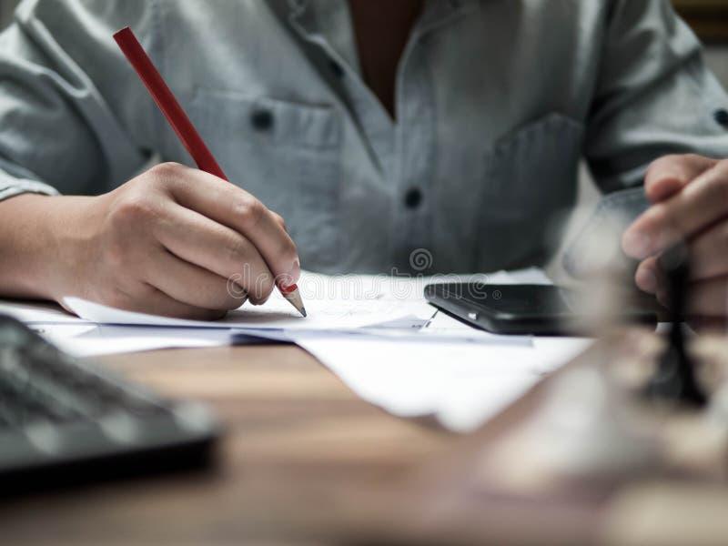 Η συνεδρίαση νεαρών άνδρων κοντά σε έναν πίνακα στο γραφείο, κρατά ένα μολύβι στο χέρι και τις εργασίες του στοκ φωτογραφία με δικαίωμα ελεύθερης χρήσης