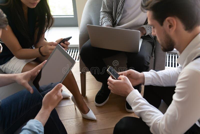 Η συνεδρίαση ομάδας επιχειρηματιών στον κύκλο που χρησιμοποιεί τις συσκευές, κλείνει επάνω στοκ φωτογραφία με δικαίωμα ελεύθερης χρήσης