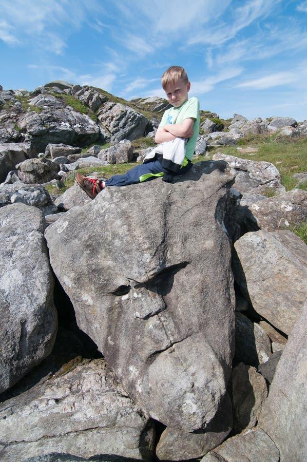 Η συνεδρίαση παιδιών στην πέτρα με μορφή του προσώπου στοκ εικόνα με δικαίωμα ελεύθερης χρήσης