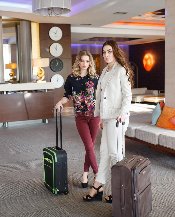 Η συνεδρίαση στην υποδοχή ξενοδοχείων, κορίτσια με τις βαλίτσες στο ξενοδοχείο πιέζει στοκ φωτογραφίες με δικαίωμα ελεύθερης χρήσης
