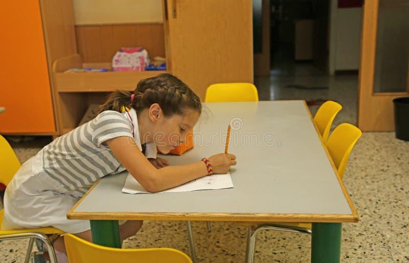 Η συνεδρίαση μικρών κοριτσιών στην κίτρινη έδρα γράφει σε χαρτί στοκ εικόνες