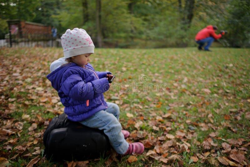 Η συνεδρίαση παιδιών σε μια μεγάλη τσάντα, και με το ενδιαφέρον εξετάζει την κινητή τηλεφωνική οθόνη στοκ εικόνες με δικαίωμα ελεύθερης χρήσης