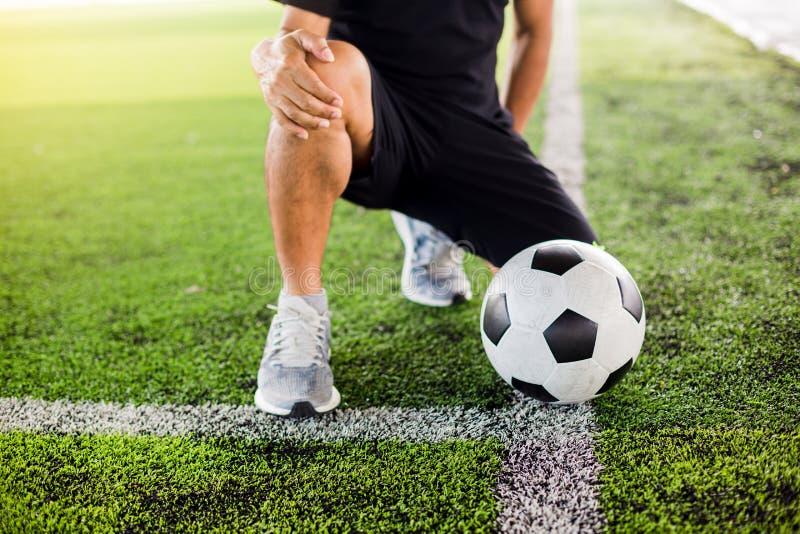 Η σφαίρα ποδοσφαίρου στην πράσινη τεχνητή τύρφη με τον ποδοσφαιριστή κάθεται και πιάνει το γόνατο στοκ φωτογραφία με δικαίωμα ελεύθερης χρήσης