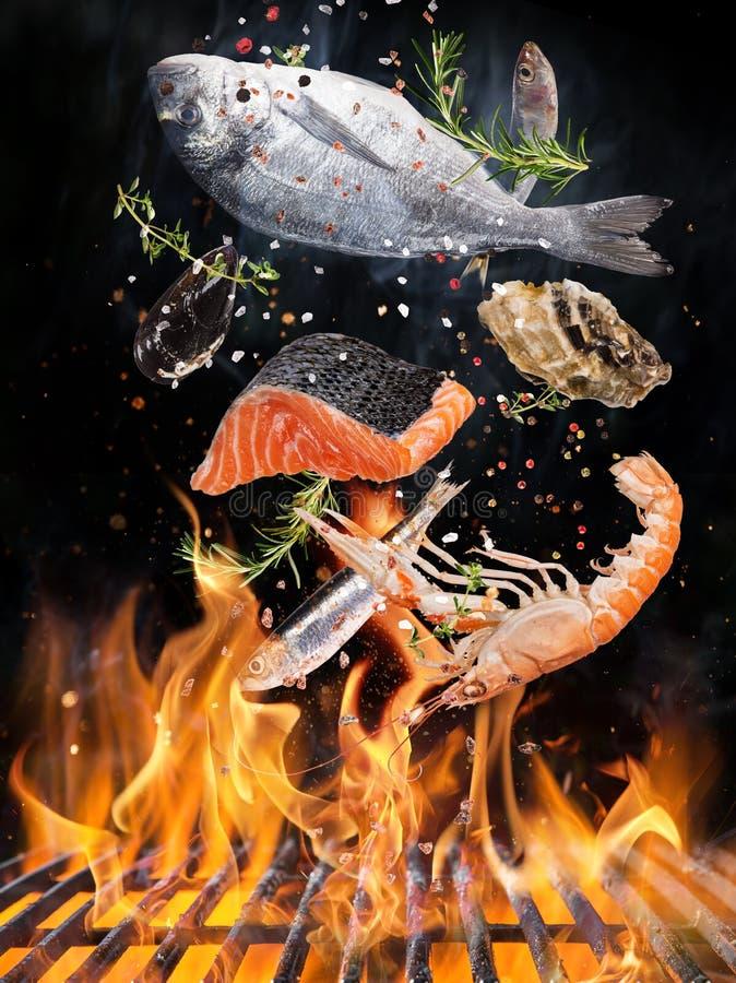 Η σχάρα κατσαρολών με τις φλόγες πυρκαγιάς, τη σχάρα χυτοσιδήρου και τη νόστιμη θάλασσα αλιεύει το πέταγμα στον αέρα στοκ φωτογραφία με δικαίωμα ελεύθερης χρήσης