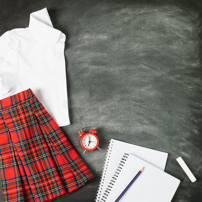 Η σχολική στολή σημειωματάριων για ένα πουκάμισο κοριτσιών περιζώνει έναν πίνακα κιμωλίας ξυπνητηριών Η έννοια πίσω στο σχολείο κ στοκ φωτογραφίες