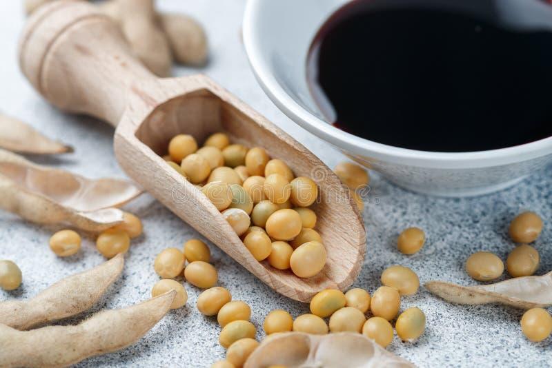 Η σόγια στο ξύλινους κουτάλι, τους λοβούς και τη σάλτσα σόγιας σε ένα λευκό κυλά σε μια γκρίζα συγκεκριμένη επιφάνεια στοκ φωτογραφία
