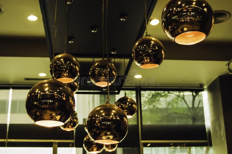 Η σύγχρονη ένωση χρώματος χαλκού πολυελαίων ύφους από το ανώτατο όριο μέσα στο εστιατόριο που έχουν τακτοποιηθεί και το εσωτερικό στοκ εικόνες