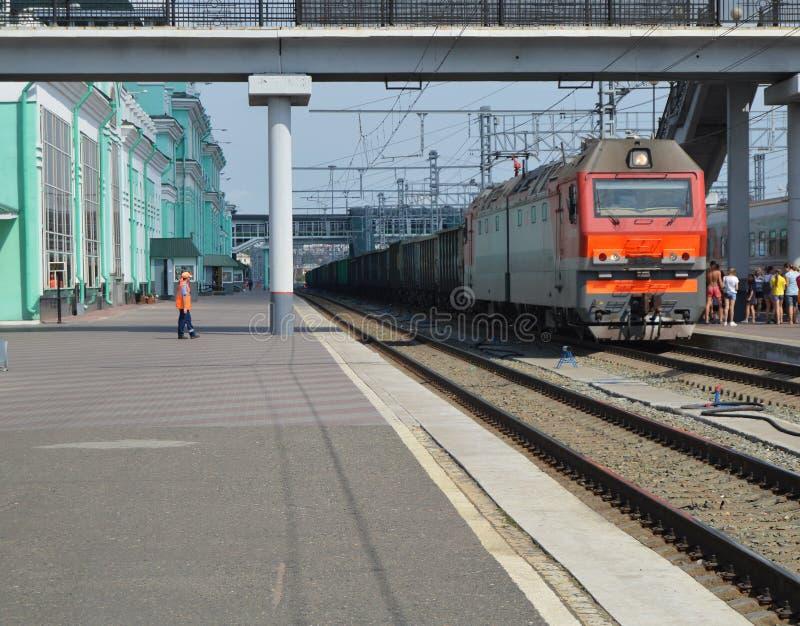 Η σύγχρονη ατμομηχανή φέρνει το φορτηγό τρένο μετά από το σιδηροδρομικό σταθμό, η έννοια της μεταφοράς στοκ εικόνα