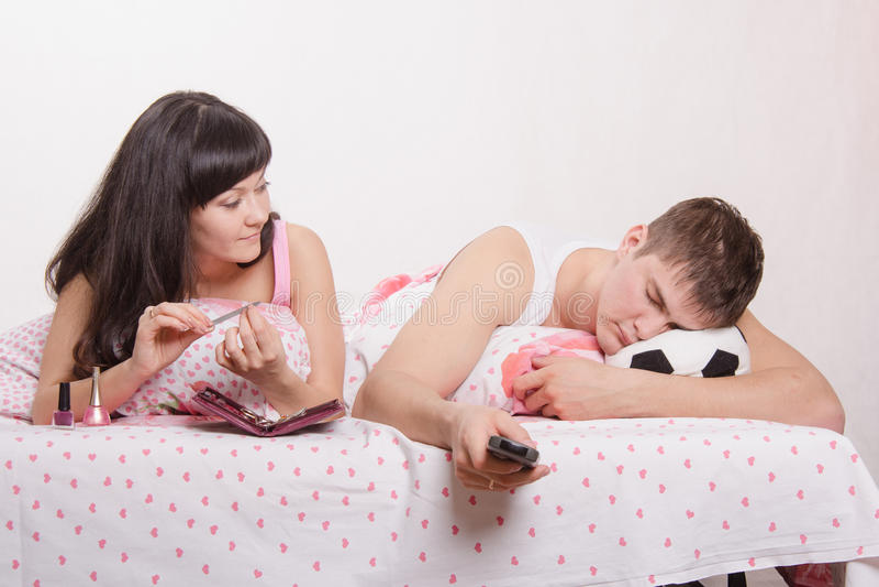Η σύζυγος εξετάζει το οπαδό ποδοσφαίρου ύπνου συζύγων της στοκ εικόνα με δικαίωμα ελεύθερης χρήσης