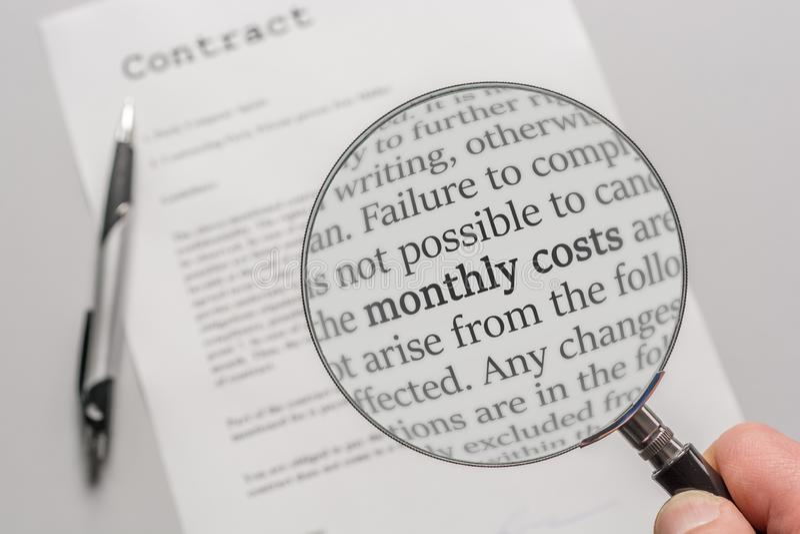 Η σύμβαση ελέγχεται με μια ενίσχυση - γυαλί σχετικά με το θέμα των μηνιαίων δαπανών ως αποτέλεσμα μιας σύμβασης στοκ εικόνα με δικαίωμα ελεύθερης χρήσης