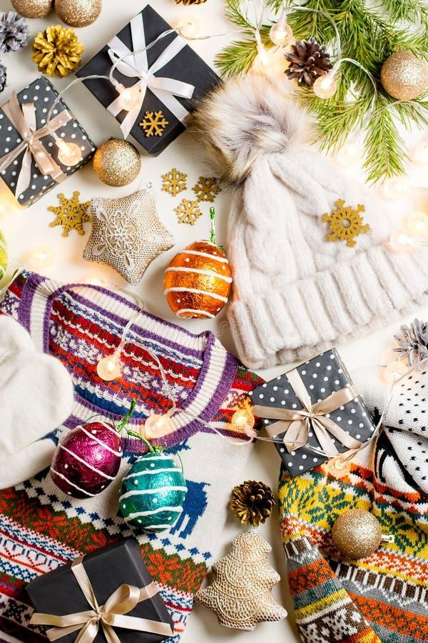 Η σύνθεση διάθεσης Χριστουγέννων με το πουλόβερ Χριστουγέννων, καπέλο, παρουσιάζει και ανάβει Το επίπεδο χειμερινής έννοιας βάζει στοκ φωτογραφία