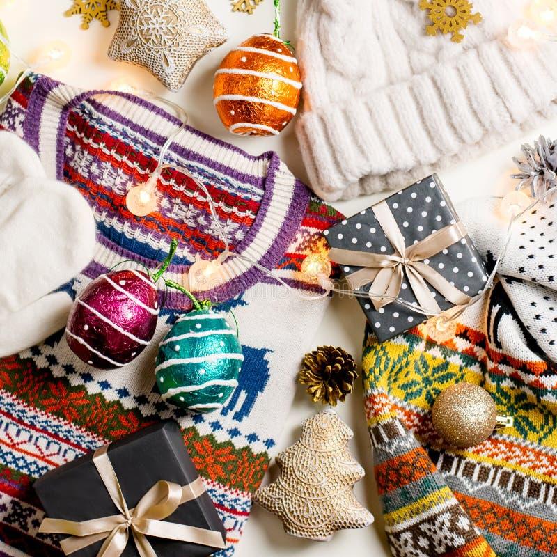 Η σύνθεση διάθεσης Χριστουγέννων με το πουλόβερ Χριστουγέννων, καπέλο, παρουσιάζει και ανάβει Το επίπεδο χειμερινής έννοιας βάζει στοκ φωτογραφία με δικαίωμα ελεύθερης χρήσης