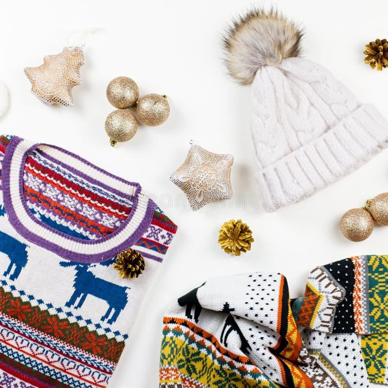 Η σύνθεση διάθεσης Χριστουγέννων με το πουλόβερ Χριστουγέννων, καπέλο, παρουσιάζει και ανάβει Το επίπεδο χειμερινής έννοιας βάζει στοκ εικόνες