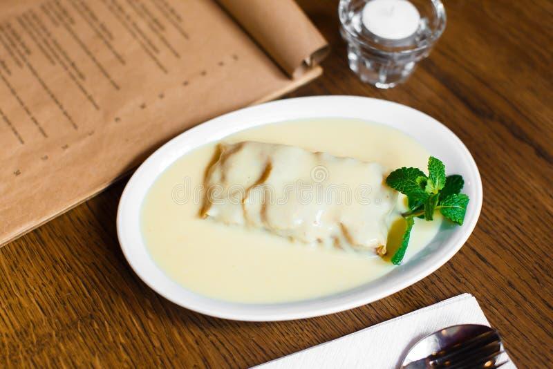 Η σύνθεση τροφίμων του επιδορπίου που καλύπτεται με την άσπρες σοκολάτα και τη μέντα Το κέικ τοποθετείται κοντά στο καλό κερί και στοκ εικόνες