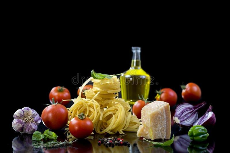 Η σύνθεση των ζυμαρικών και των λαχανικών στο μαύρο υπόβαθρο στοκ εικόνα με δικαίωμα ελεύθερης χρήσης