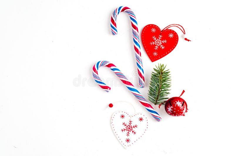 Η σύνθεση Χριστουγέννων με την καραμέλα Χριστουγέννων, οι κλάδοι δέντρων και οι διακοπές διακοσμούν στο άσπρο υπόβαθρο Επίπεδος β στοκ εικόνες