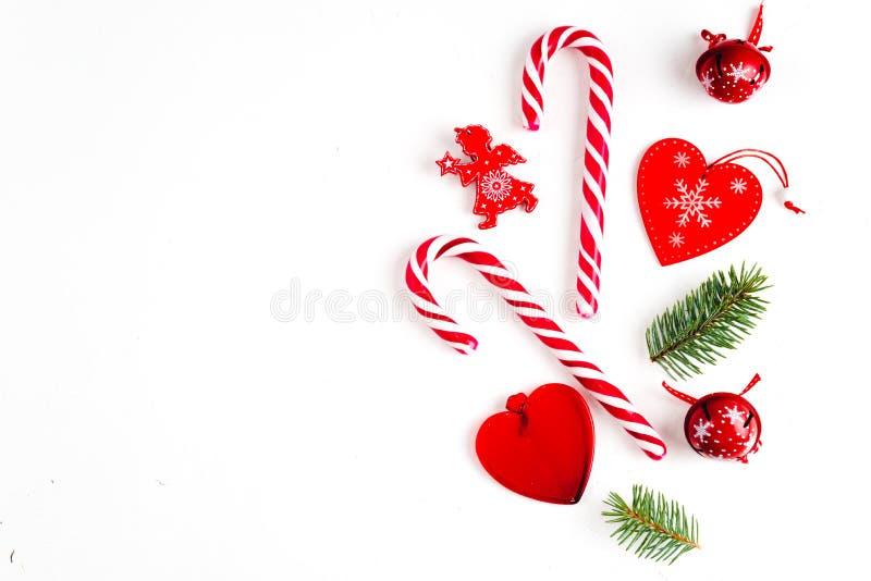 Η σύνθεση Χριστουγέννων με την καραμέλα Χριστουγέννων, οι κλάδοι δέντρων και οι διακοπές διακοσμούν στο άσπρο υπόβαθρο Επίπεδος β στοκ φωτογραφία