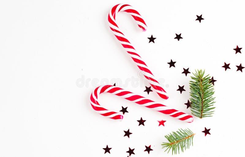 Η σύνθεση Χριστουγέννων με την καραμέλα Χριστουγέννων, οι κλάδοι δέντρων και οι διακοπές διακοσμούν στο άσπρο υπόβαθρο r στοκ εικόνα με δικαίωμα ελεύθερης χρήσης