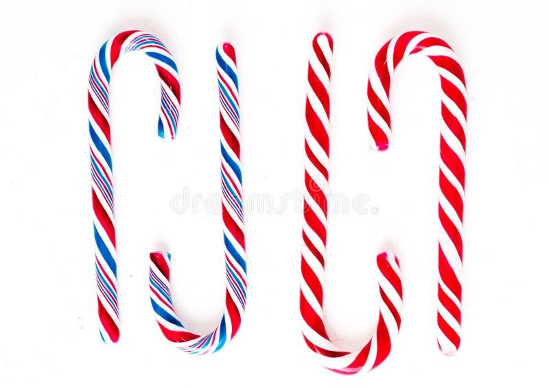 Η σύνθεση Χριστουγέννων με την καραμέλα Χριστουγέννων, οι κλάδοι δέντρων και οι διακοπές διακοσμούν στο άσπρο υπόβαθρο r στοκ εικόνες