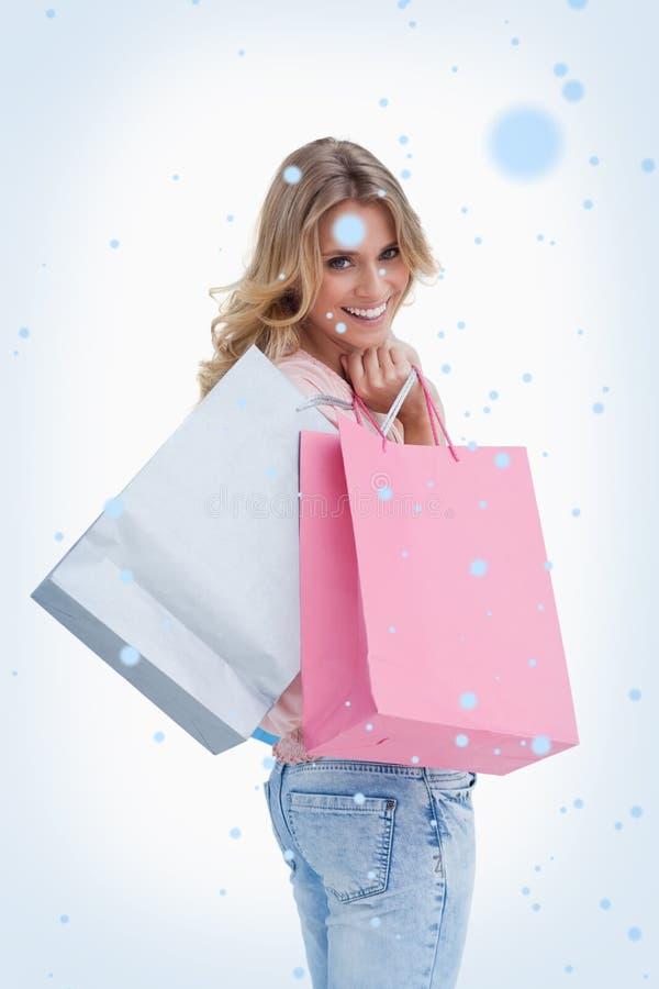 Η σύνθετη εικόνα μιας γυναίκας που εξετάζει πίσω τη κάμερα φέρνει τις τσάντες αγορών πέρα από τον ώμο της στοκ φωτογραφίες
