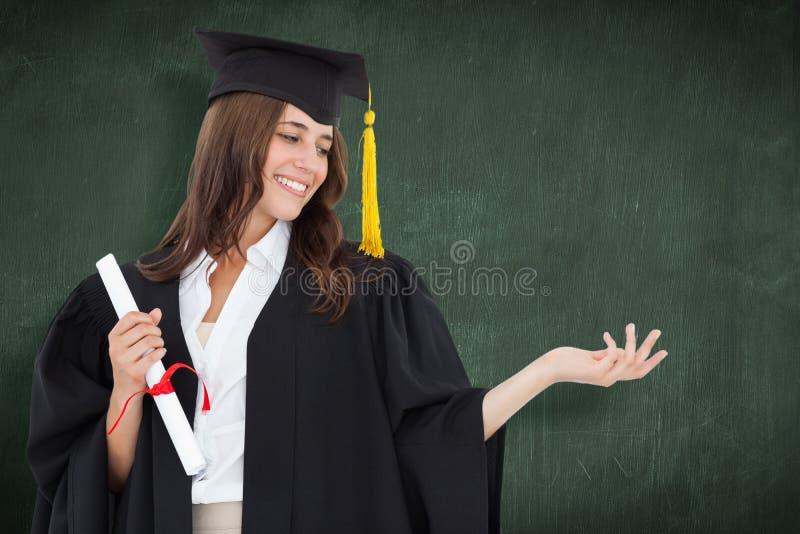 Η σύνθετη εικόνα μιας γυναίκας που κρατά την διανέμει με έναν βαθμό σε την άλλο χέρι καθώς χαμογελά στοκ εικόνα με δικαίωμα ελεύθερης χρήσης