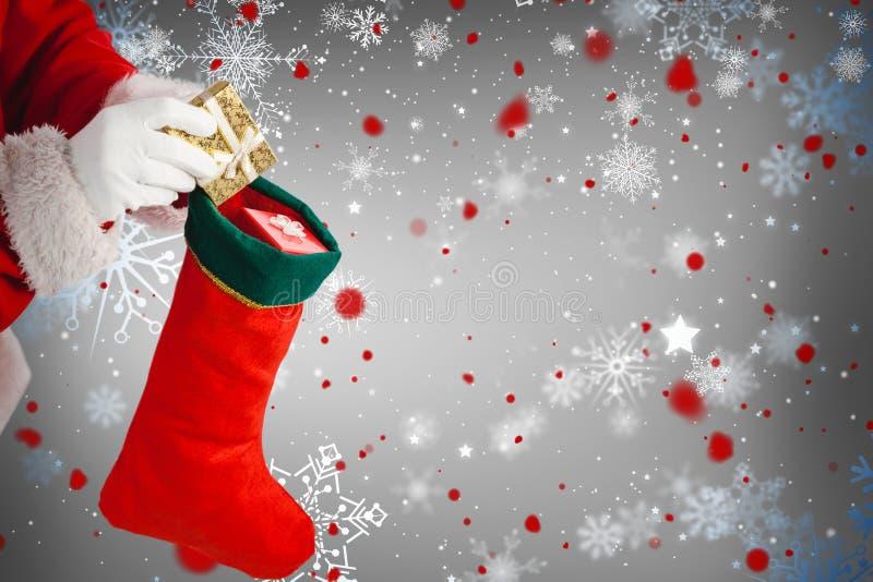 Η σύνθετη εικόνα της τοποθέτησης Άγιου Βασίλη παρουσιάζει στις γυναικείες κάλτσες Χριστουγέννων στοκ φωτογραφία