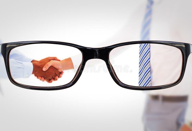 Η σύνθετη εικόνα τινάγματος επιχειρηματιών χαμόγελου του νέου παραδίδει το γραφείο στοκ φωτογραφίες