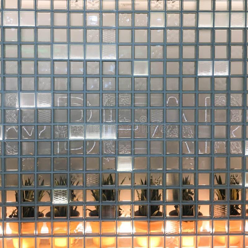 Η σύσταση ενός γυαλιού χάρασε το διαφανές τετραγωνικό παχύ μικρό διακοσμητικό κεραμίδι με τα διαφορετικά σχέδια και με τις πράσιν στοκ φωτογραφίες