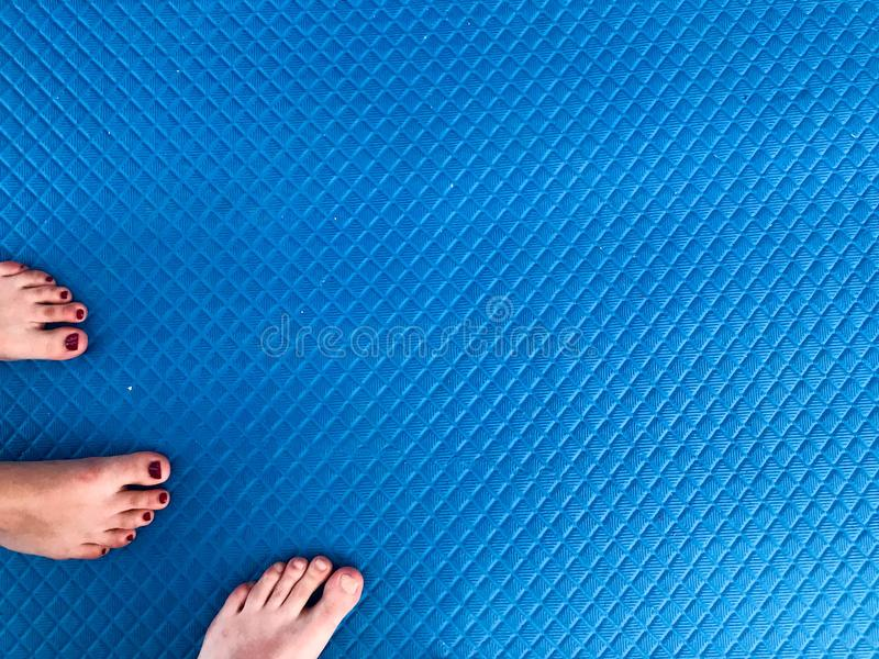 Η σύσταση με τα αρσενικά και θηλυκά πόδια, πόδια με ένα όμορφο κόκκινο μανικιούρ στα δάχτυλα στέκεται σε ένα μπλε λαστιχένιο αντι στοκ εικόνες