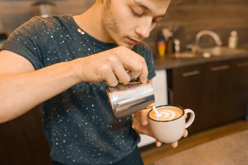 Η τέχνη καφέ, κινηματογράφηση σε πρώτο πλάνο του νέου αρσενικού γάλακτος εκμετάλλευσης barista για προετοιμάζει το φλιτζάνι του κ στοκ εικόνες