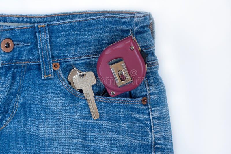 Η ταινία-γραμμή και τα κλειδιά για το σπίτι σε ένα keychain βρίσκονται σε μια δευτερεύουσα τσέπη του τζιν παντελόνι στοκ εικόνες