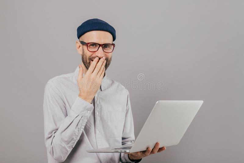 Η ταλαντούχος αρσενική γραφική εργασία σχεδιαστών μακρινά για τη συσκευή, γέλια θετικά, στόμα καλύψεων με το φοίνικα, φορά τα γυα στοκ φωτογραφία με δικαίωμα ελεύθερης χρήσης