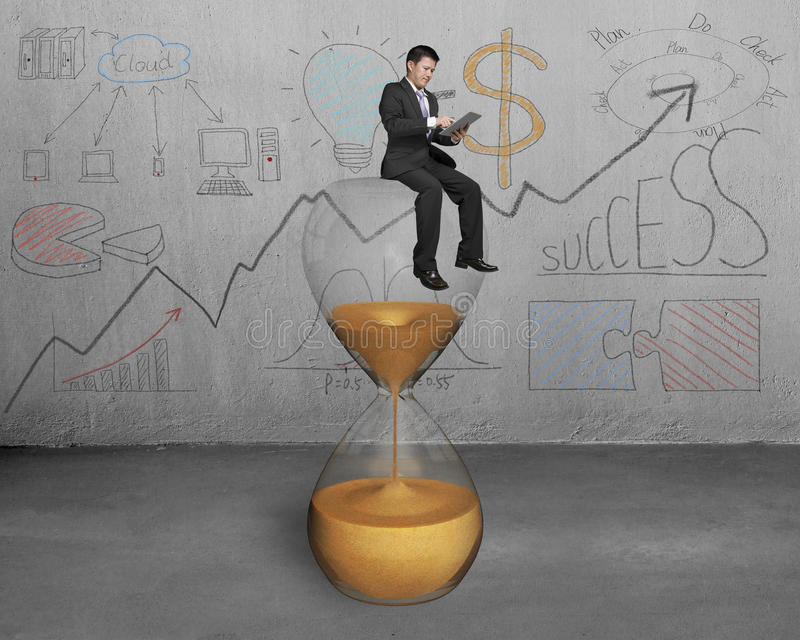 Η ταμπλέτα χρήσης επιχειρηματιών και κάθεται στο γυαλί ώρας απεικόνιση αποθεμάτων