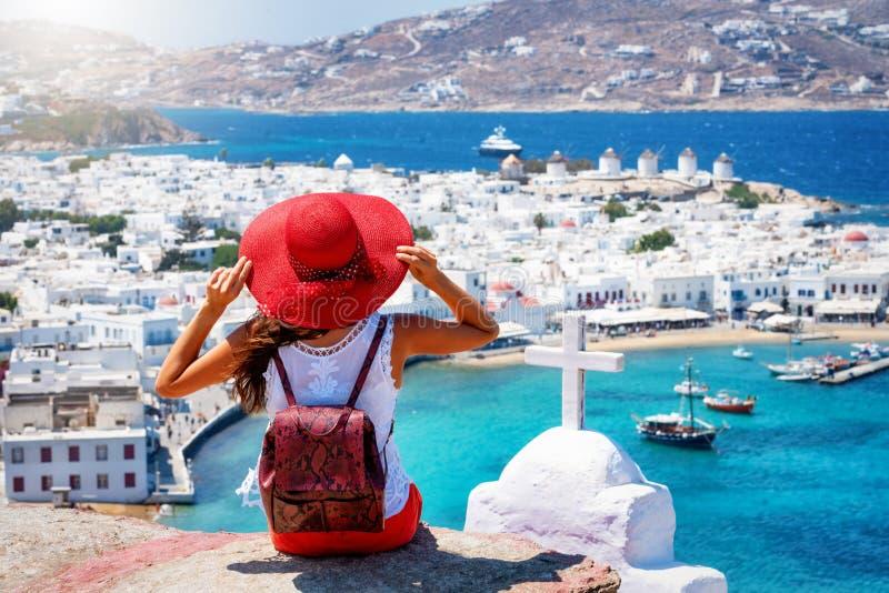 Η ταξιδιωτική γυναίκα απολαμβάνει τη θέα πέρα από την πόλη του νησιού της Μυκόνου, Κυκλάδες, Ελλάδα στοκ εικόνα