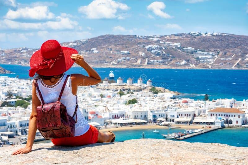 Η ταξιδιωτική γυναίκα απολαμβάνει τη θέα σχετικά με έναν λόφο πέρα από την άσπρη πόλη του νησιού της Μυκόνου στοκ εικόνες