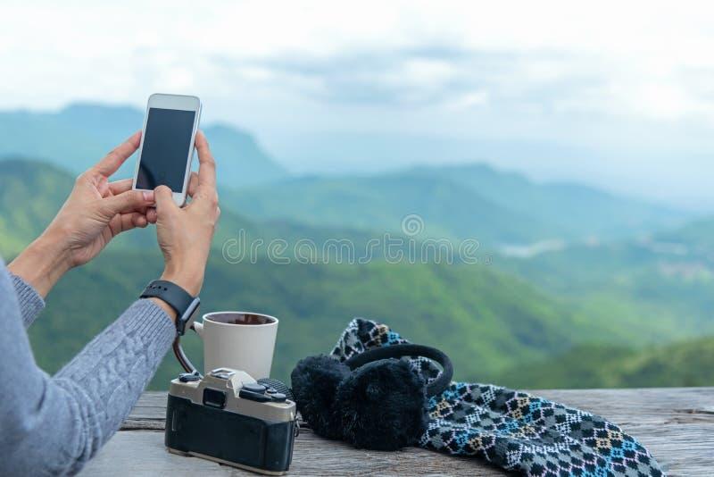 Η ταξιδιωτική γυναίκα χρησιμοποιώντας το smartphone και πίνοντας τον καφέ και το τσάι και παίρνει μια φωτογραφία και χαλαρώνει στ στοκ εικόνα με δικαίωμα ελεύθερης χρήσης