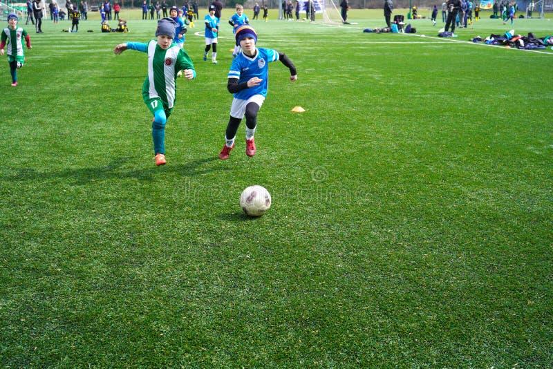 Η ταχύτητα ποδοσφαιριστών αγοριών τρέχει στη σφαίρα βλαστών στο στόχο στην πράσινη χλόη Μια σκηνή του αγώνα ποδοσφαίρου ενός αγορ στοκ φωτογραφία