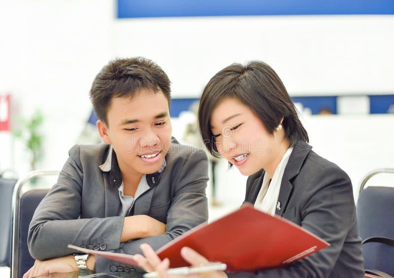 Η ταϊλανδική (ασιατική) επιχείρηση copule λειτουργεί μαζί σε ένα πρόγραμμα γραφείων στοκ φωτογραφία