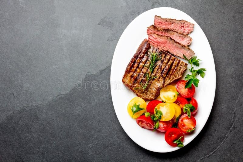 Η τεμαχισμένη μέση σπάνια ψημένη στη σχάρα μπριζόλα βόειου κρέατος εξυπηρέτησε στο άσπρο πιάτο με τη σαλάτα ντοματών και τις σφαί στοκ φωτογραφία με δικαίωμα ελεύθερης χρήσης