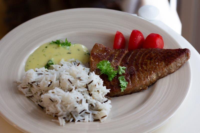 Η τηγανισμένη φέτα της λωρίδας τόνου με το ρύζι διακοσμεί επάνω με τη σάλτσα στο άσπρο πιάτο στοκ εικόνες με δικαίωμα ελεύθερης χρήσης